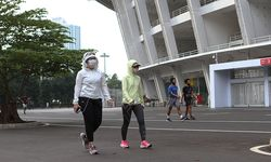 Para pelaku olahraga beradaptasi dengan menggunakan masker sambil berolahraga di ring road Stadion U