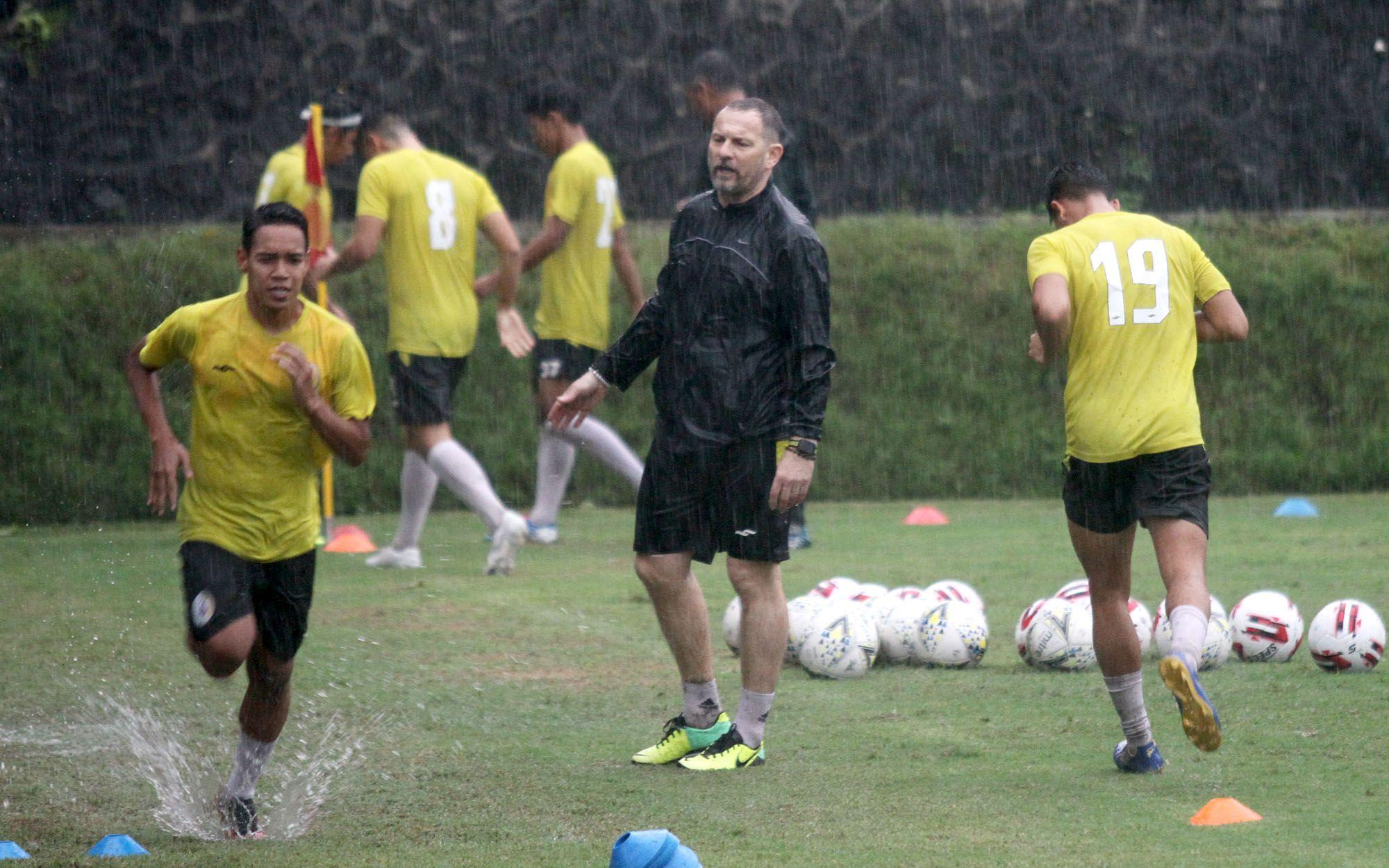 Pelatih PSS Sleman, Dejan Antonic (tengah), mengawasi pemain PSS berlatih dalam guyuran hujan di Lapangan Universitas Islam Indonesia, Yogyakarta, Selasa, 3 Maret 2020.