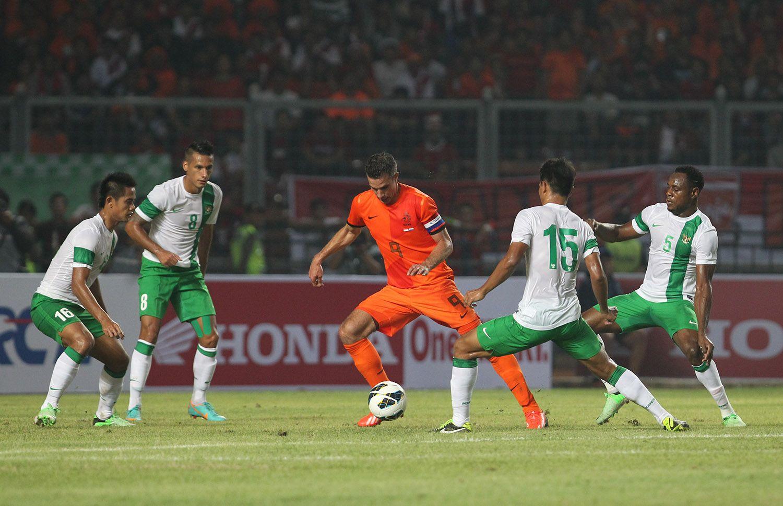 Kapten timnas Belanda, Robin van Persie (tengah) dikawal empat peman timnas Indonesia dalam laga uji coba di Stadion Utomo Gelora Bung Karno pada 2013.