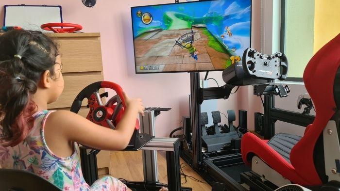 Seorang anak terlihat sedang memainkan Mario Kart Deluxe 8 di Nintendo Switch dengan menggunakan mesin simulasi balapan yang ternyata dibuat sendiri oleh sang ayah, Chris Aaron.