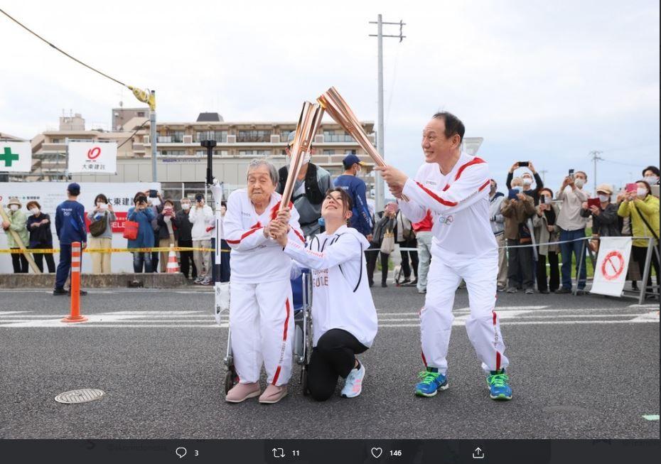 Momen Shigeko Kagawa menerima api abadi olimpiade dalam reli obor Olimpiade Tokyo di Perfektur Nara.