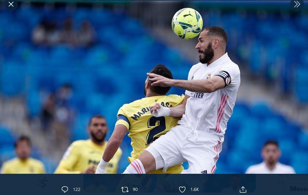 Penyerang Real Madrid, Karim Benzema, saat duel udara dengan pemain Villarreal dalam laga Liga Spanyol, Sabtu (22/5/2021).