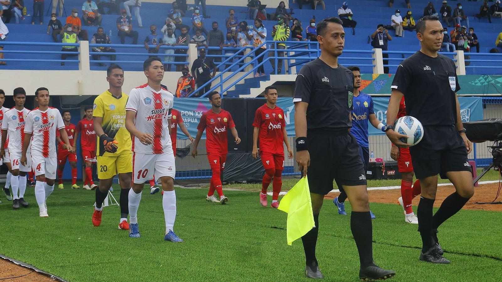 Wasit Fariq Hitaba (kanan) memimpin ofisial laga dan pemain Sulawesi Utara dan Aceh saat memasuki lapangan dalam pertandingan sepak bola putra PON XX Papua 2021 di Stadion Barnabas Youwe pada 2 September 2021.
